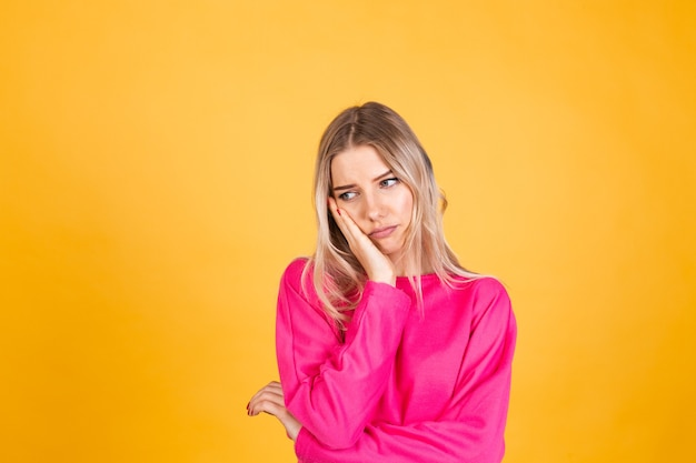 Mujer bonita europea en blusa rosa sobre pared amarilla
