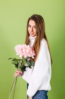 Mujer bonita europea en suéter blanco casual aislado, mirada romántica con ramo de flores rosadas con sonrisa