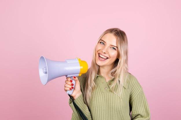 Mujer bonita europea en suéter casual con megáfono en pared rosa