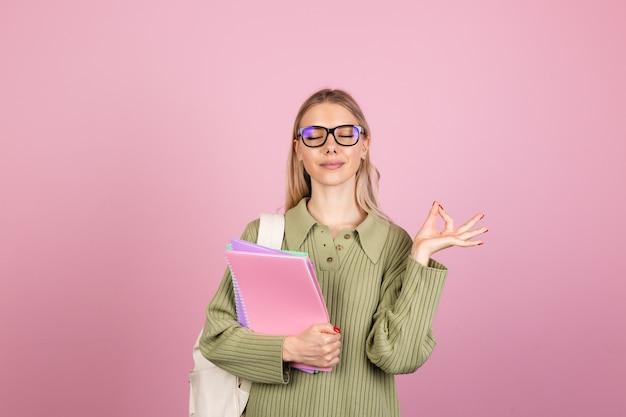 Mujer bonita europea en suéter casual en pared rosa