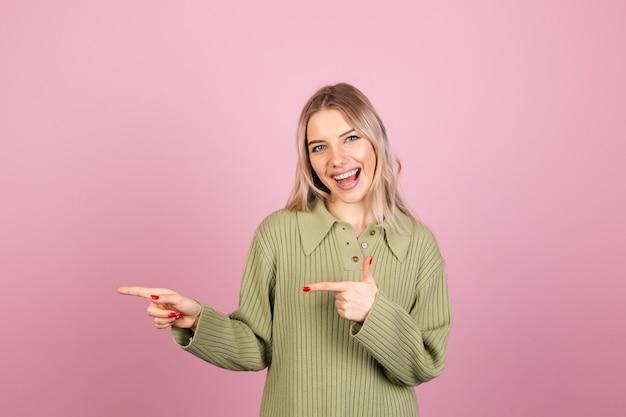 Mujer bonita europea en suéter de punto casual en pared rosa
