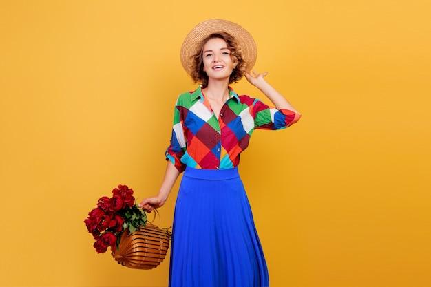 Mujer bonita europea en vestido azul con ramo de flores sobre fondo amarillo. sombrero de copa. humor de verano.