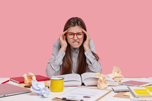 Mujer bonita con exceso de trabajo muerde el labio inferior, sufre de dolor de cabeza, lee un artículo científico en un libro, tiene desorden en la mesa