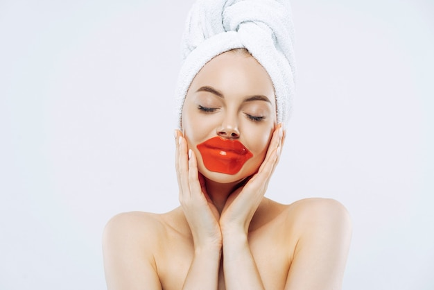 Mujer bonita con expresión tranquila, cierra los ojos, aplica parches en los labios, usa maquillaje natural, toalla envuelta en la cabeza, se para los hombros descubiertos en el interior, fondo blanco