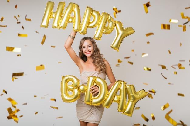 Mujer bonita feliz celebrando un cumpleaños en confeti dorado