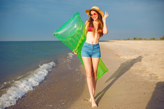 Mujer bonita feliz divirtiéndose en la playa, vistiendo ropa de playa elegante, sombrero de bikini y pantalones cortos de mezclilla, piernas largas, cuerpo delgado, sosteniendo colchón de aire y caminando cerca del océano.