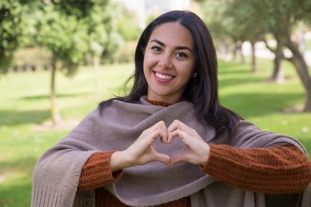 Mujer bonita feliz que hace gesto del corazón en parque de la ciudad
