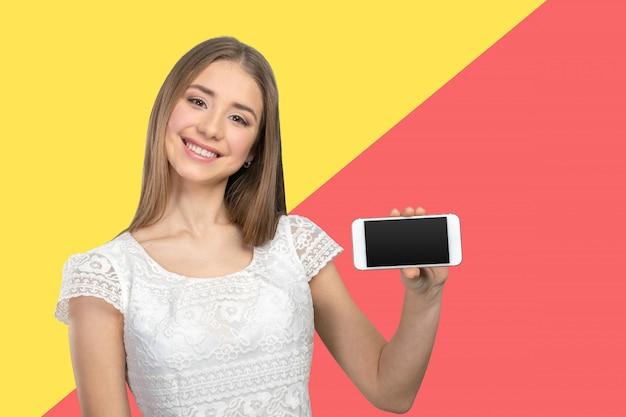 Mujer bonita feliz que muestra una pantalla de teléfono en blanco
