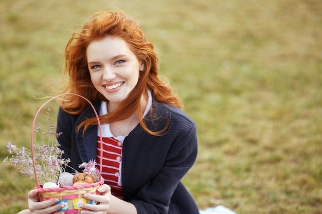 Mujer bonita feliz que sostiene la cesta de picnic con los huevos de pascua al aire libre