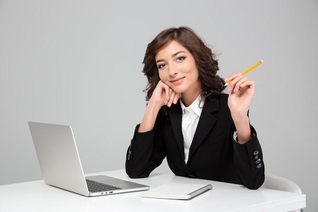 Mujer bonita feliz sonriente rizada joven que trabaja con la computadora portátil y que escribe en el cuaderno
