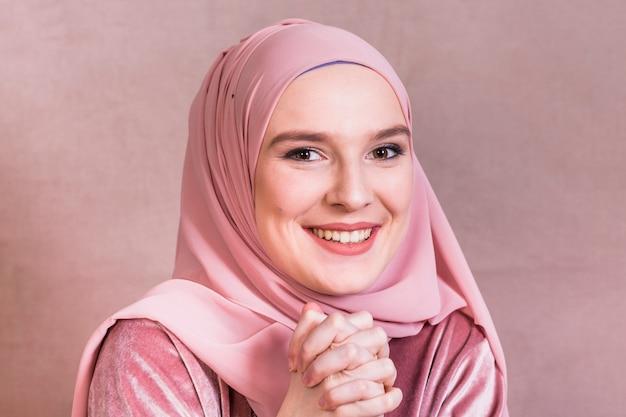 Mujer bonita feliz con sus manos juntas sobre fondo coloreado