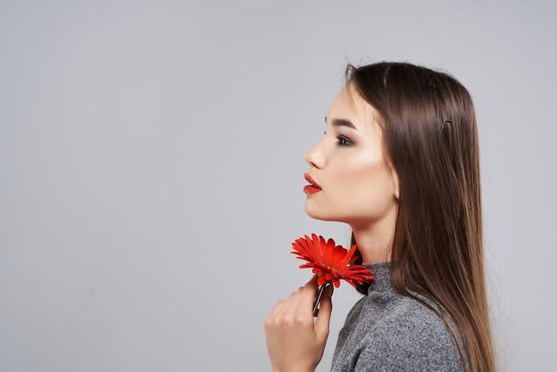 Mujer bonita con flor roja cerca de maquillaje brillante de cara de cerca