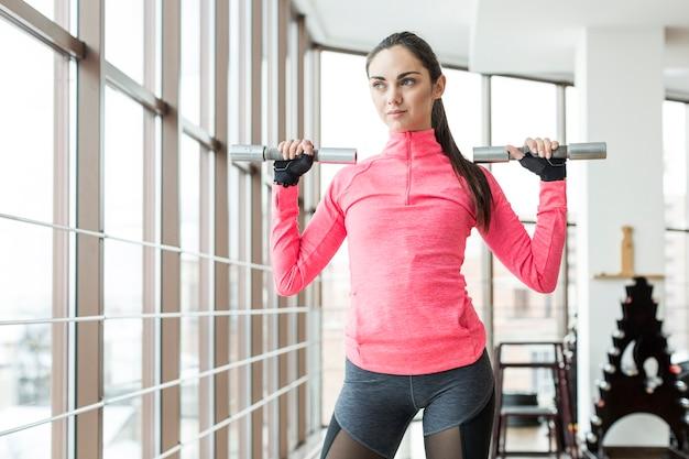 Mujer bonita forma sosteniendo pesas