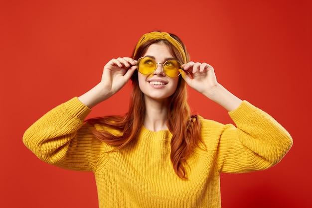 Mujer bonita con gafas suéter amarillo emociones ropa casual fondo rojo. foto de alta calidad