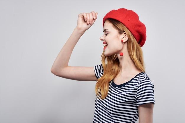 Mujer bonita en un gesto de labios rojos de camiseta a rayas con su estudio de modelo de manos