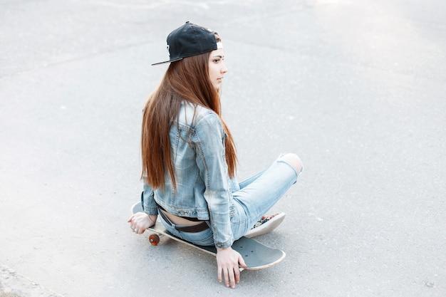 Mujer bonita en una gorra de béisbol y ropa de mezclilla sentada en una patineta