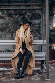 Mujer bonita hablando por teléfono y esperando el autobús