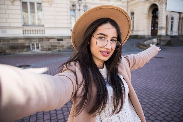 Mujer bonita hacer selfie en su nuevo teléfono inteligente al aire libre en la ciudad en un día soleado