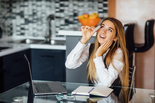 Mujer bonita hermosa usa spray para los ojos, sintiéndose bien después de un uso prolongado de la computadora portátil, sentada en casa