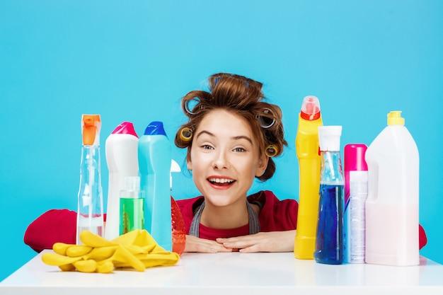 La mujer bonita con las herramientas de limpieza sonríe y parece contenta
