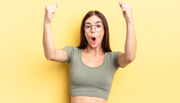 Mujer bonita hispana celebrando un éxito increíble como una ganadora, luciendo emocionada y feliz diciendo ¡toma eso!