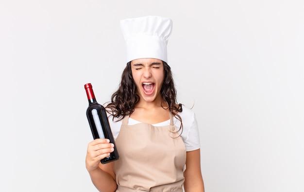 Mujer bonita hispana chef gritando agresivamente, mirando muy enojado y sosteniendo una botella de vino