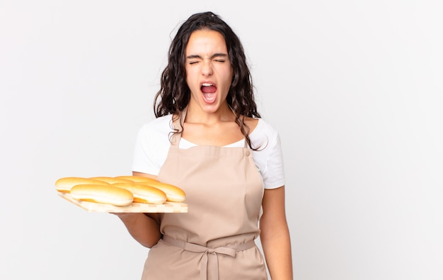 Mujer bonita hispana chef gritando agresivamente, mirando muy enojado y sosteniendo un pan troy bollos