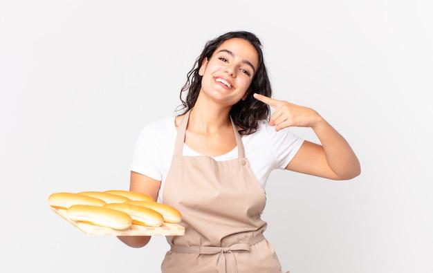 Mujer bonita hispana chef sonriendo con confianza apuntando a su propia amplia sonrisa y sosteniendo un pan troy bollos