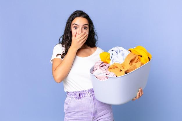 Mujer bonita hispana cubriendo la boca con las manos con un sorprendido y sosteniendo una canasta de lavado de ropa