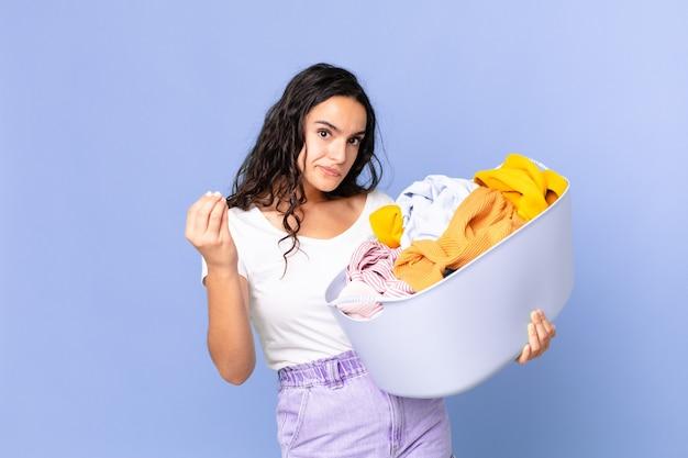 Mujer bonita hispana haciendo gesto de capice o dinero, diciéndole que pague y sosteniendo una canasta de lavado de ropa