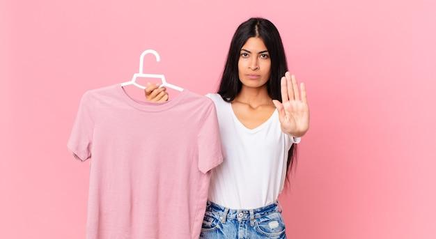 Mujer bonita hispana mirando seriamente mostrando la palma abierta haciendo gesto de parada y sosteniendo un paño elegido