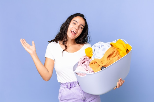 Mujer bonita hispana que se siente feliz, sorprendida al darse cuenta de una solución o idea y sosteniendo una canasta de lavado de ropa