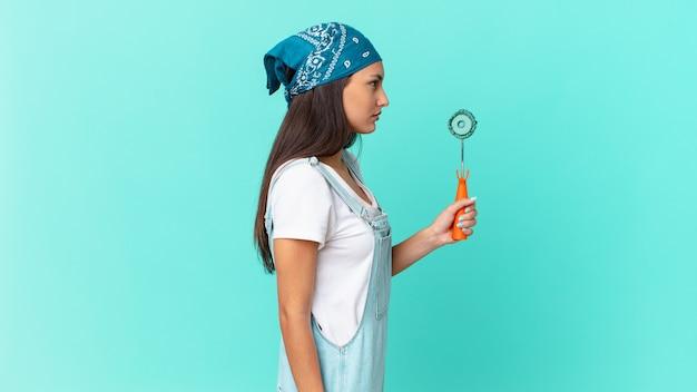 Mujer bonita hispana en vista de perfil pensando, imaginando o soñando despierto. concepto de casa de pintura
