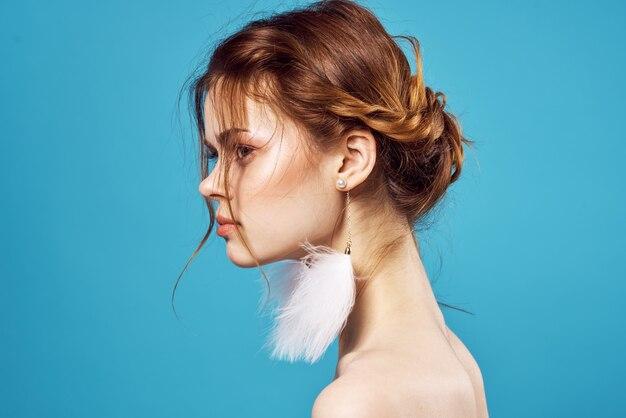 Mujer bonita hombros desnudos pendientes joyería moda fondo azul