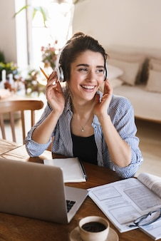 Mujer bonita inteligente en auriculares escuchando música mientras trabaja o estudia en la computadora portátil en casa
