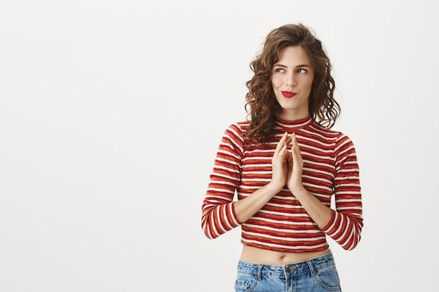 Mujer bonita inteligente planeando un plan perfecto, dedos de aguja y mirando a la izquierda
