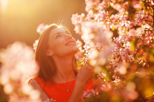 Mujer bonita en el jardín de verano que huele el manzano floreciente