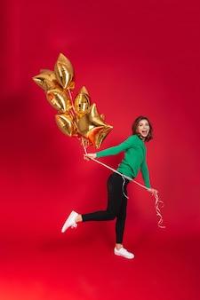 Mujer bonita joven alegre que sostiene los globos.