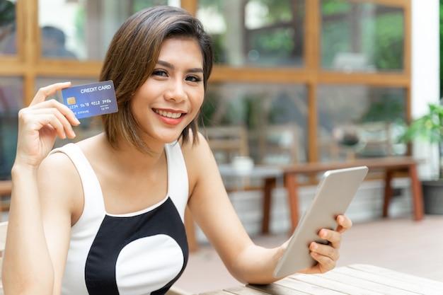 Mujer bonita joven alegre utiliza tarjeta cradit