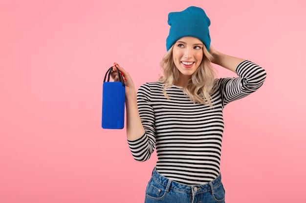Mujer bonita joven con altavoz inalámbrico escuchando música con camisa a rayas y sombrero azul sonriendo feliz estado de ánimo positivo posando sobre fondo rosa