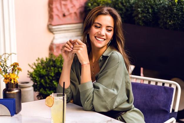 Mujer bonita joven bebiendo un sabroso cóctel dulce en la terraza de la ciudad, traje casual de moda, fin de semana y estado de ánimo de viaje