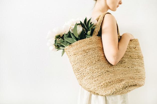 Mujer bonita joven con bolsa de paja con ramo de flores de peonía blanca sobre fondo blanco. concepto de moda de verano.