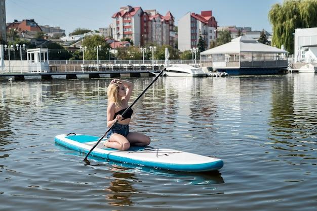 Mujer bonita joven a bordo de sup disfruta del estilo de vida de verano en el lago de la ciudad