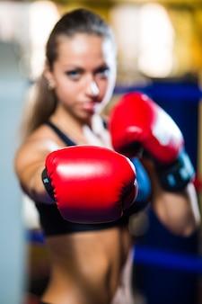 Mujer bonita joven boxeador de pie en el ring y haciendo ejercicio con saco de boxeo