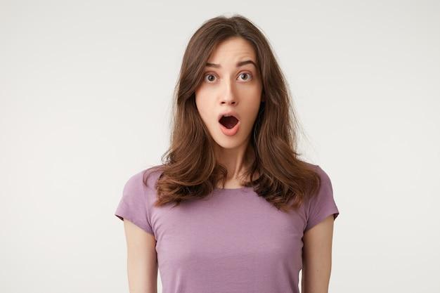 Mujer bonita joven con un cabello hermoso se ve sorprendido, estupefacto, con la mandíbula caída