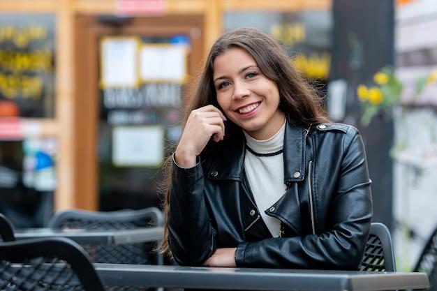 Mujer bonita joven con cabello largo y oscuro sentado en una mesa en un café al aire libre y esperando amigos