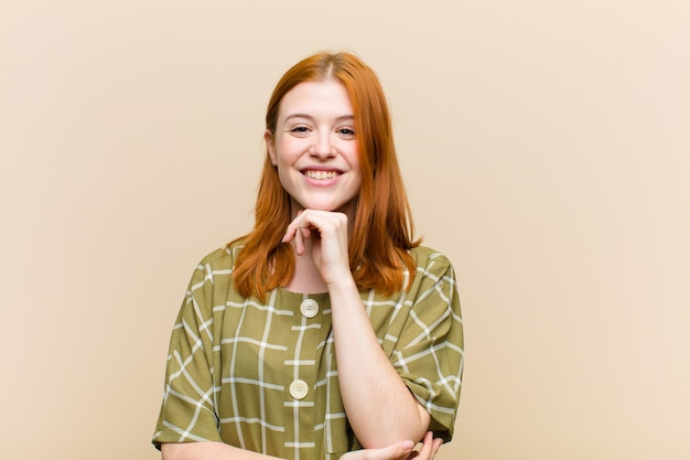 Mujer bonita joven de cabeza roja que parece feliz y sonriente con la mano en la barbilla, preguntándose o haciendo una pregunta, comparando opciones