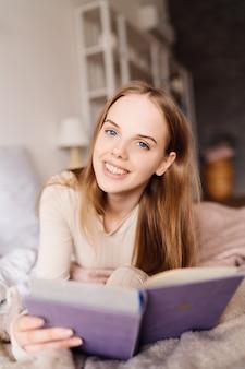 Mujer bonita joven en la cama en casa disfrutando de su libro favorito