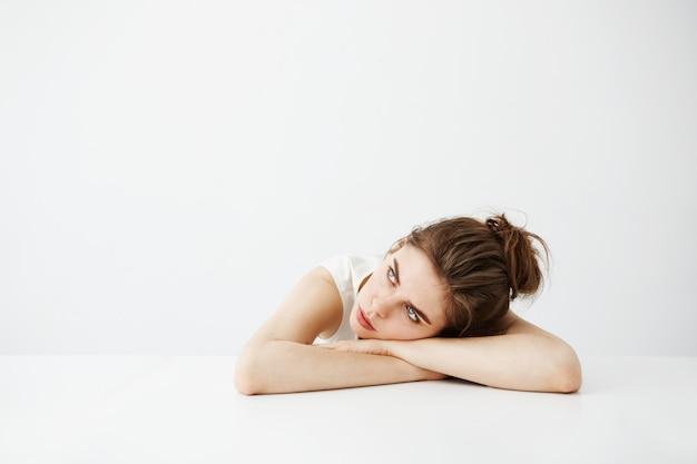 Mujer bonita joven cansada aburrida con el bollo que piensa soñando la mentira en la tabla sobre el fondo blanco.