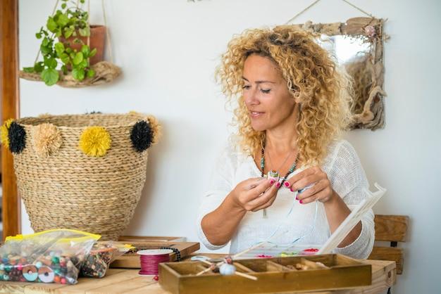 Mujer bonita joven en casa hacer creaciones de joyas hechas a mano con abalorios